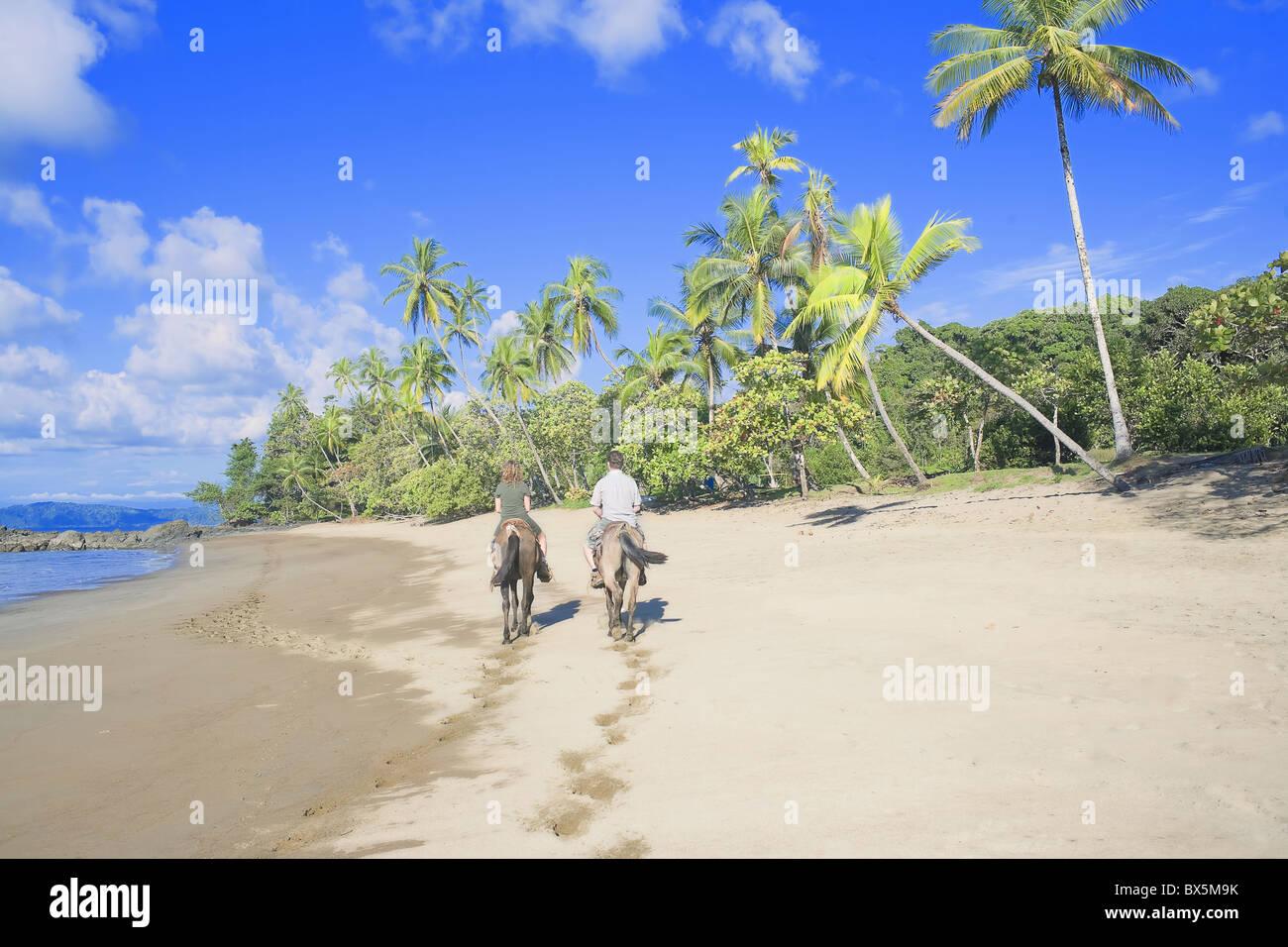 Horseback riding on tropical beach, Baia Drake, Osa Peninsula, Costa Rica, Central America - Stock Image