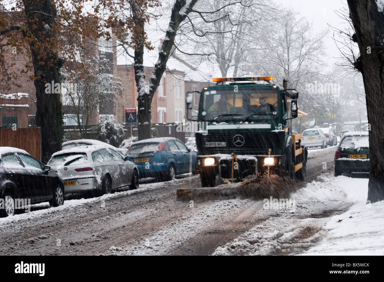 A gritting lorry, with a snow plough, spreading grit or salt on a suburban road in South London during a snowstorm - Stock Image