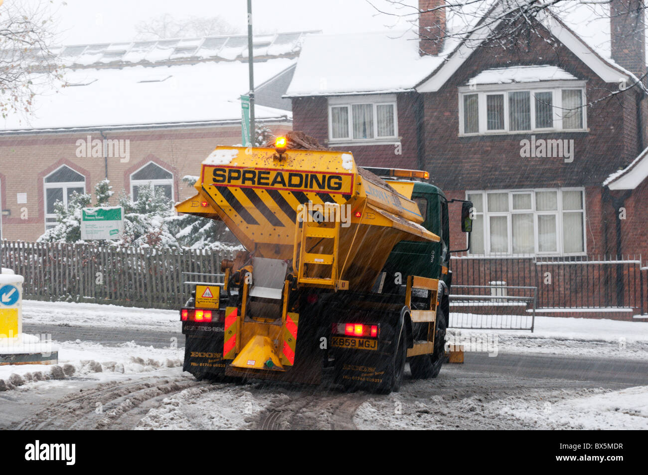 A gritting lorry spreading grit or salt over a suburban road in South London during a snowstorm - Stock Image