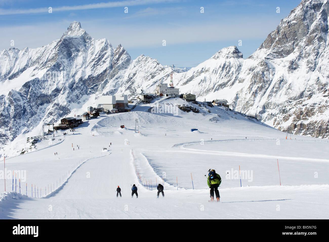 Skiers skiing on a ski run, mountain scenery in Cervinia ski resort, Cervinia, Valle d'Aosta, Italian Alps, - Stock Image