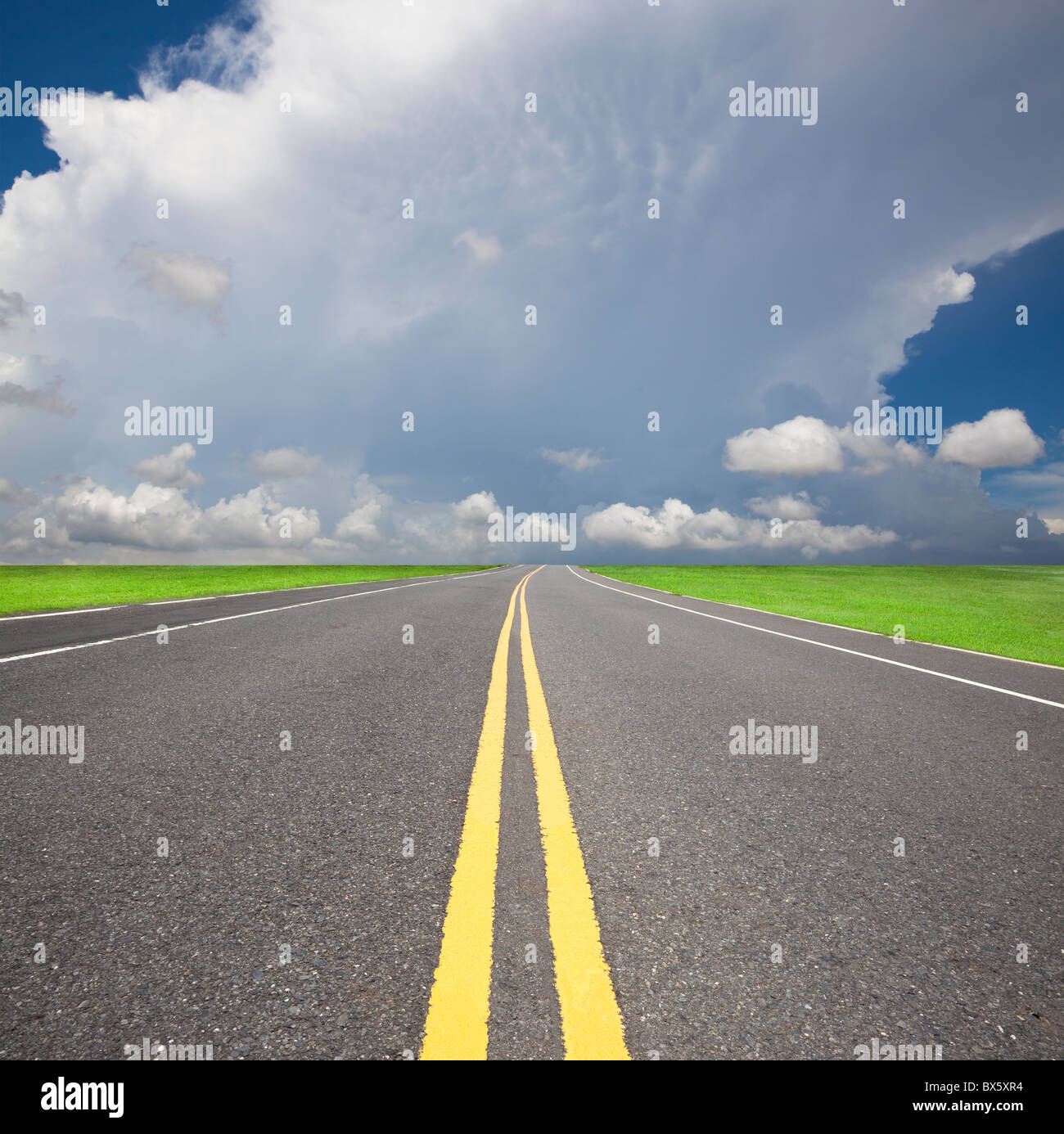 empty country road pass through the storm and cloud - Stock Image