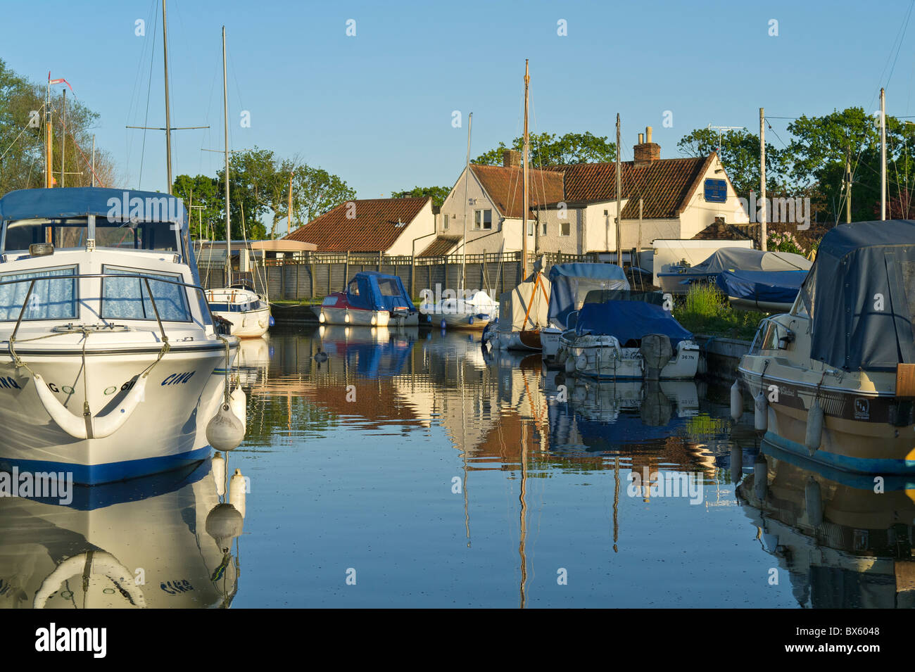 Boats Moored at Hickling Parish Staithe Norfolk UK and Pleasure Boat Inn - Stock Image