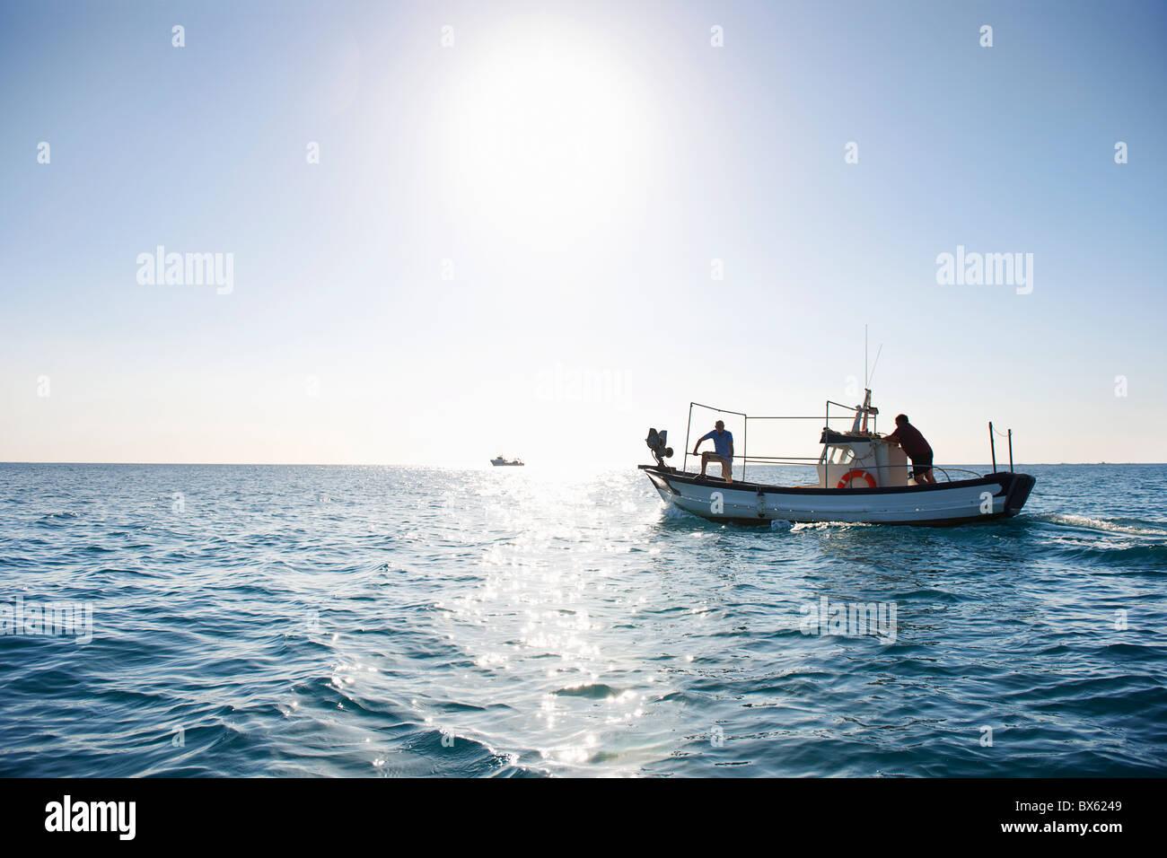 Fishermen on fishing boat at sea - Stock Image