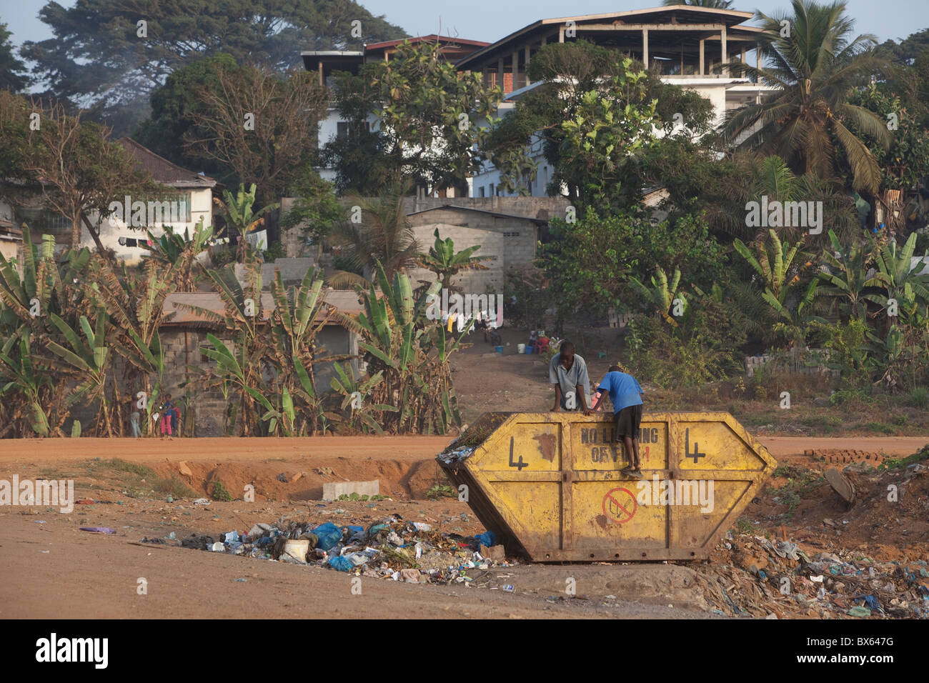 city scene along oceanfront showing children digging through trash