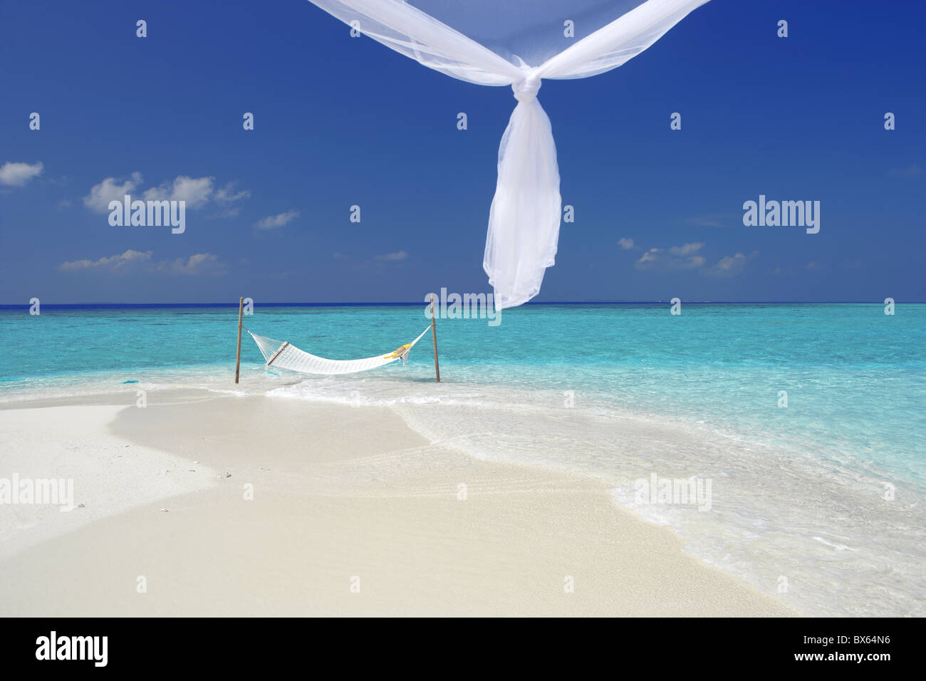 Hammock hanging in shallow clear water, The Maldives, Indian Ocean, Asia - Stock Image
