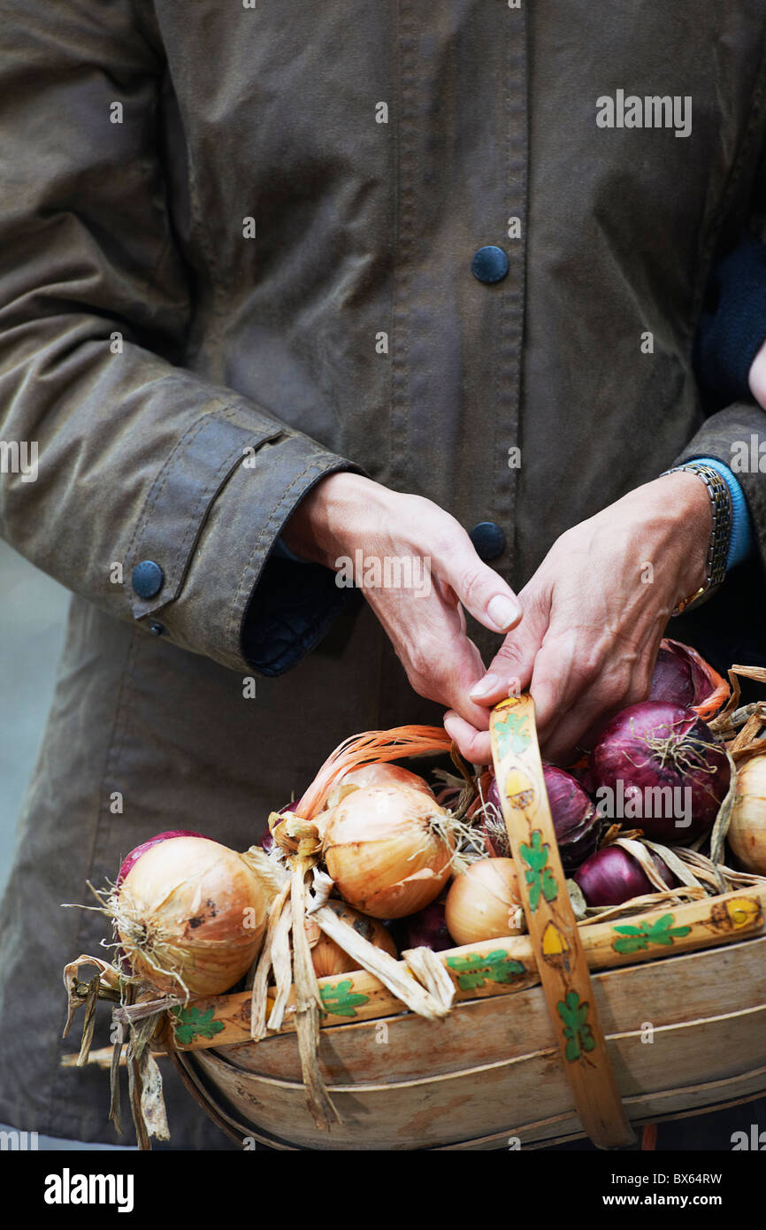 Grandmother holding basket of onions - Stock Image