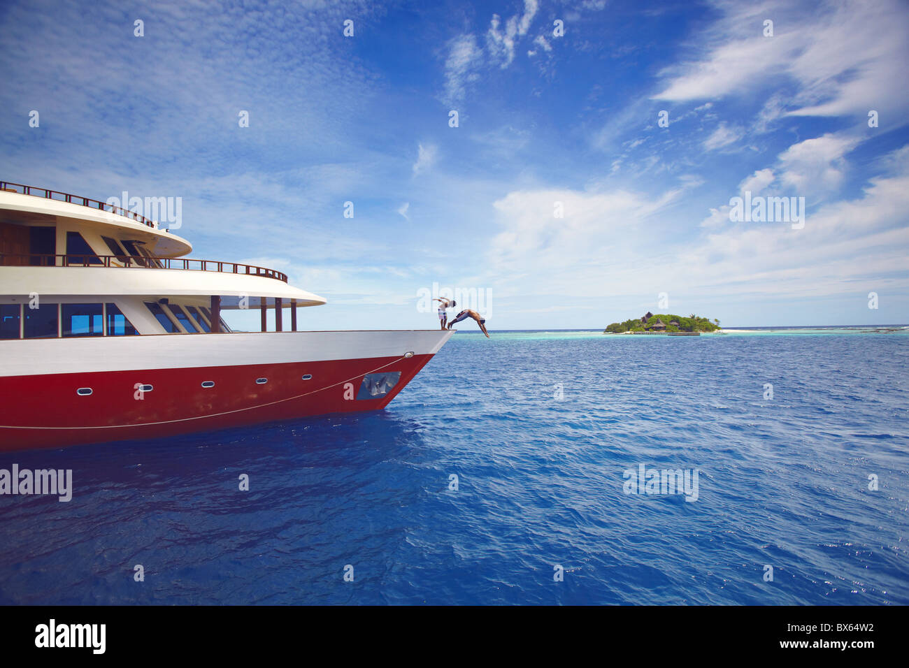 Young people jumping from boat into sea, Maldives, Indian Ocean, Asia - Stock Image