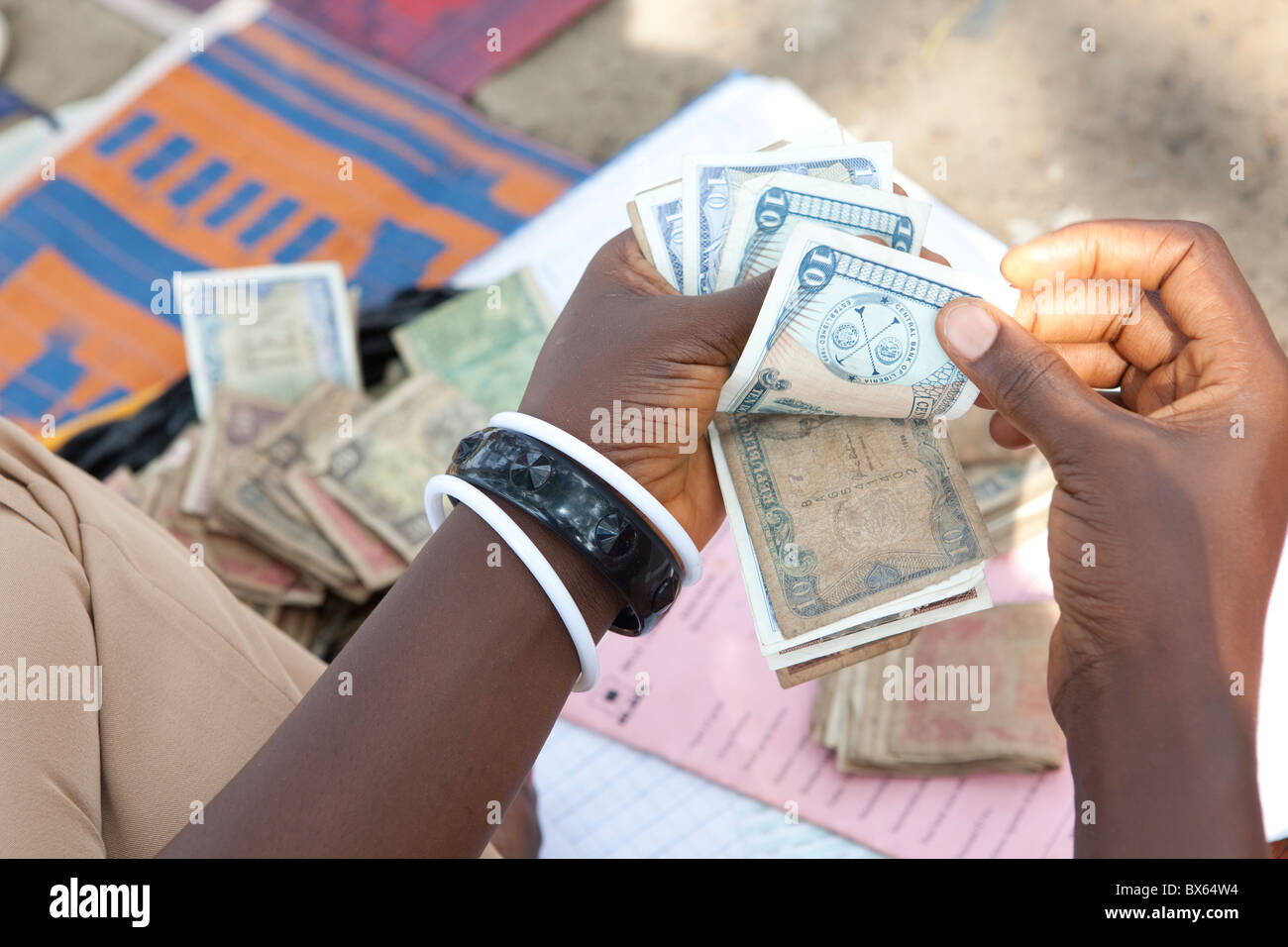 A woman counts Liberian dollars in Kakata, Liberia, West Africa. - Stock Image