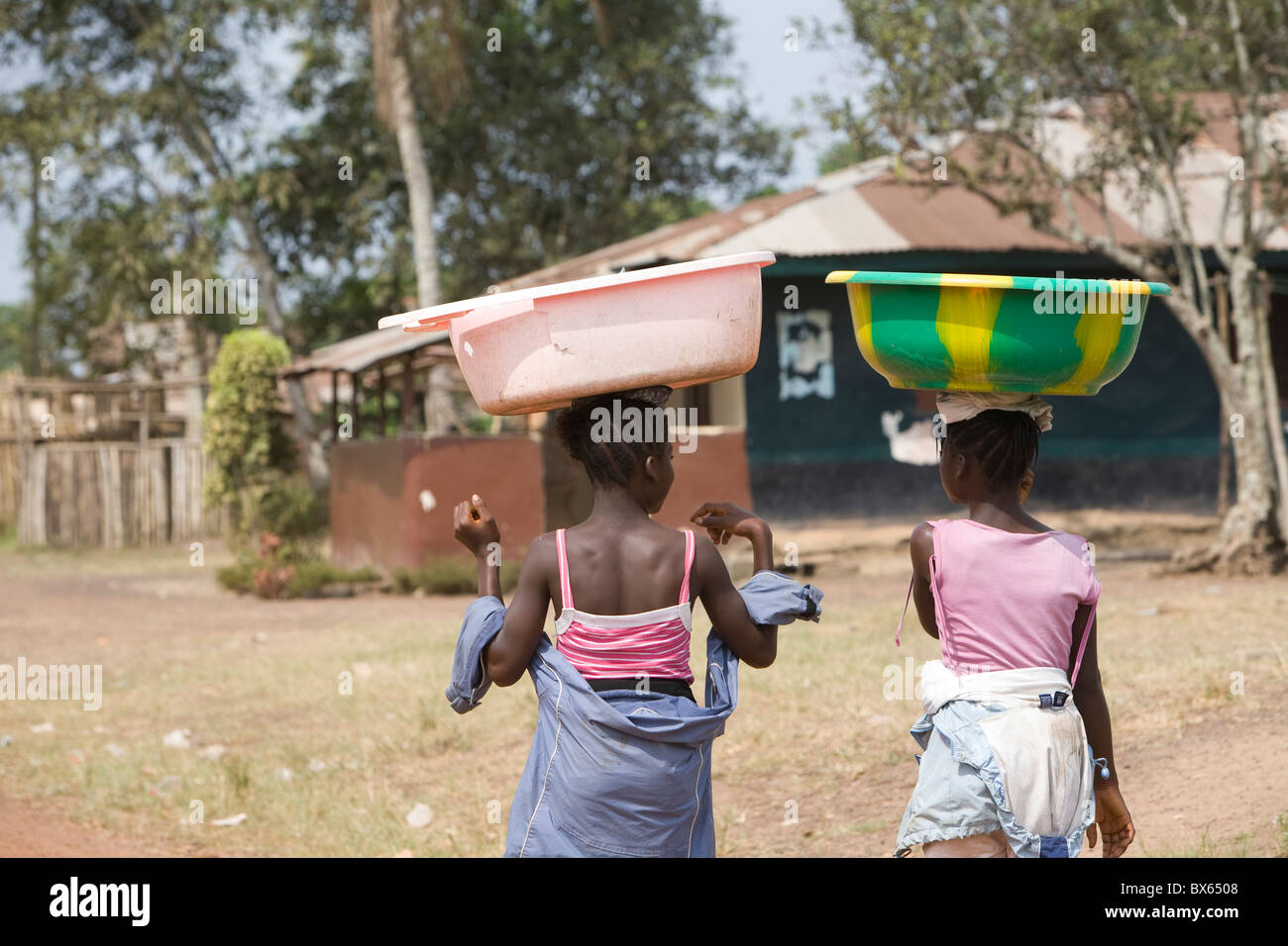 Girls with buckets balanced on their heads walk along the main street in Kakata, Liberia, West Africa. - Stock Image