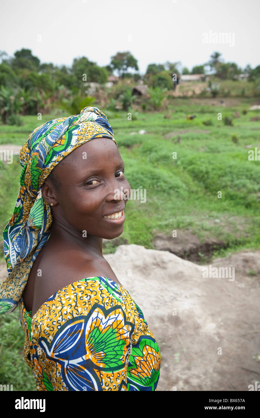 A woman in stands in an open field Kakata, Liberia, West Africa. - Stock Image