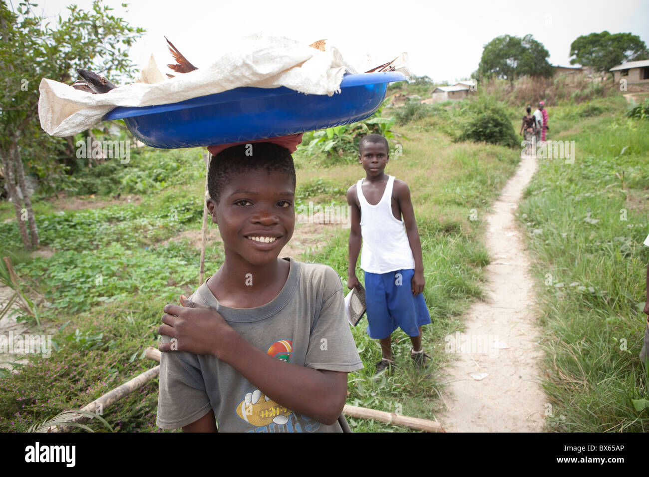 Villagers walk along a path in Kakata, Liberia, West Africa. - Stock Image