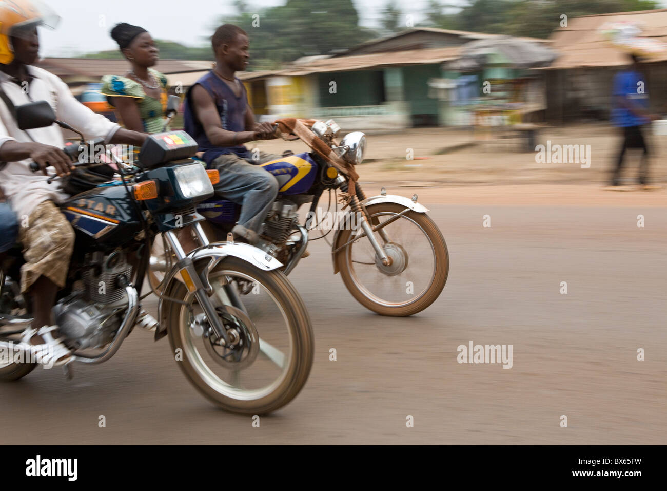 Motorcycles speed down a street in Monrovia, Liberia, West Africa. - Stock Image