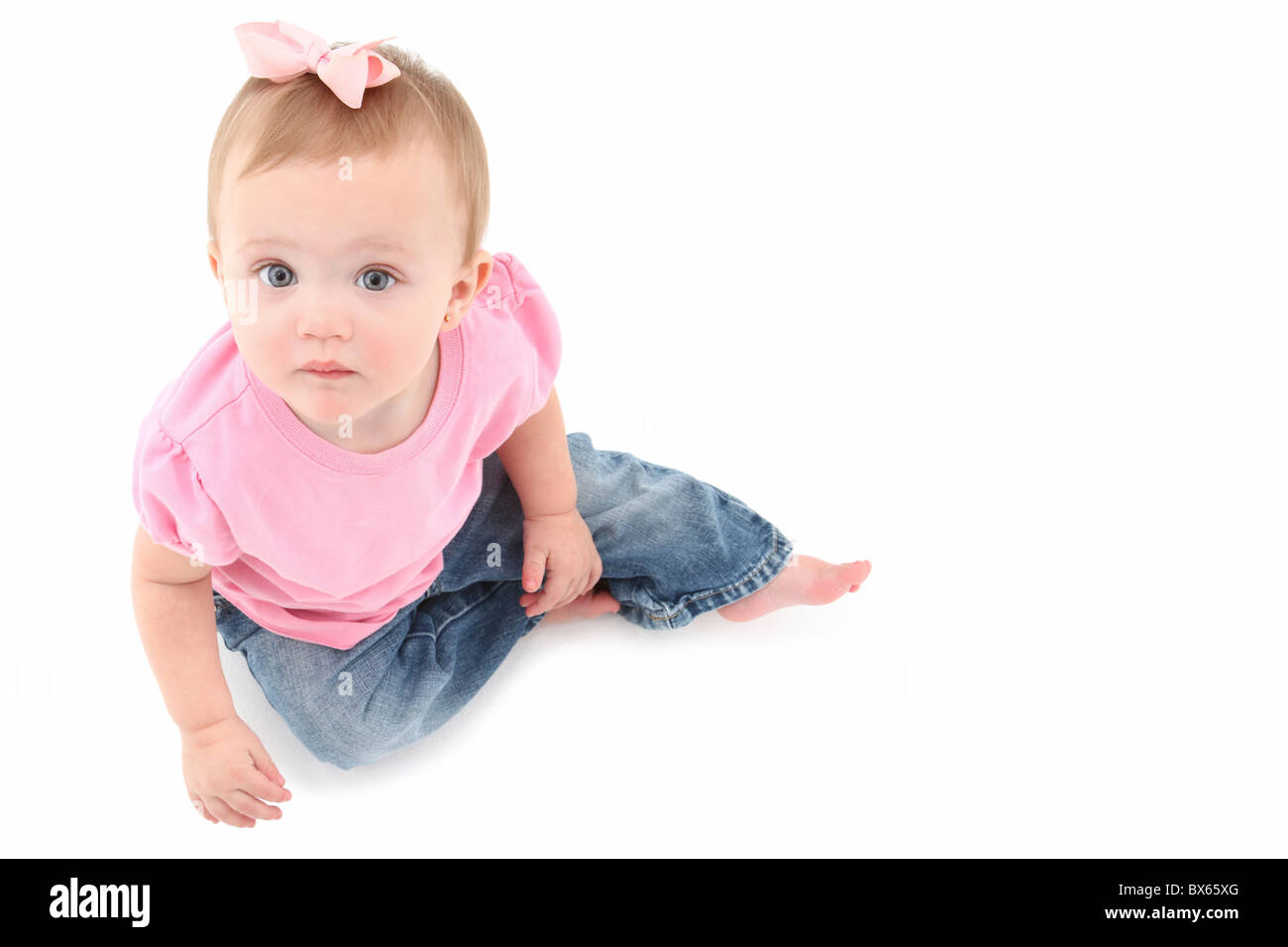 Adorable 10 month old baby girl sitting and looking up at camera over white. - Stock Image
