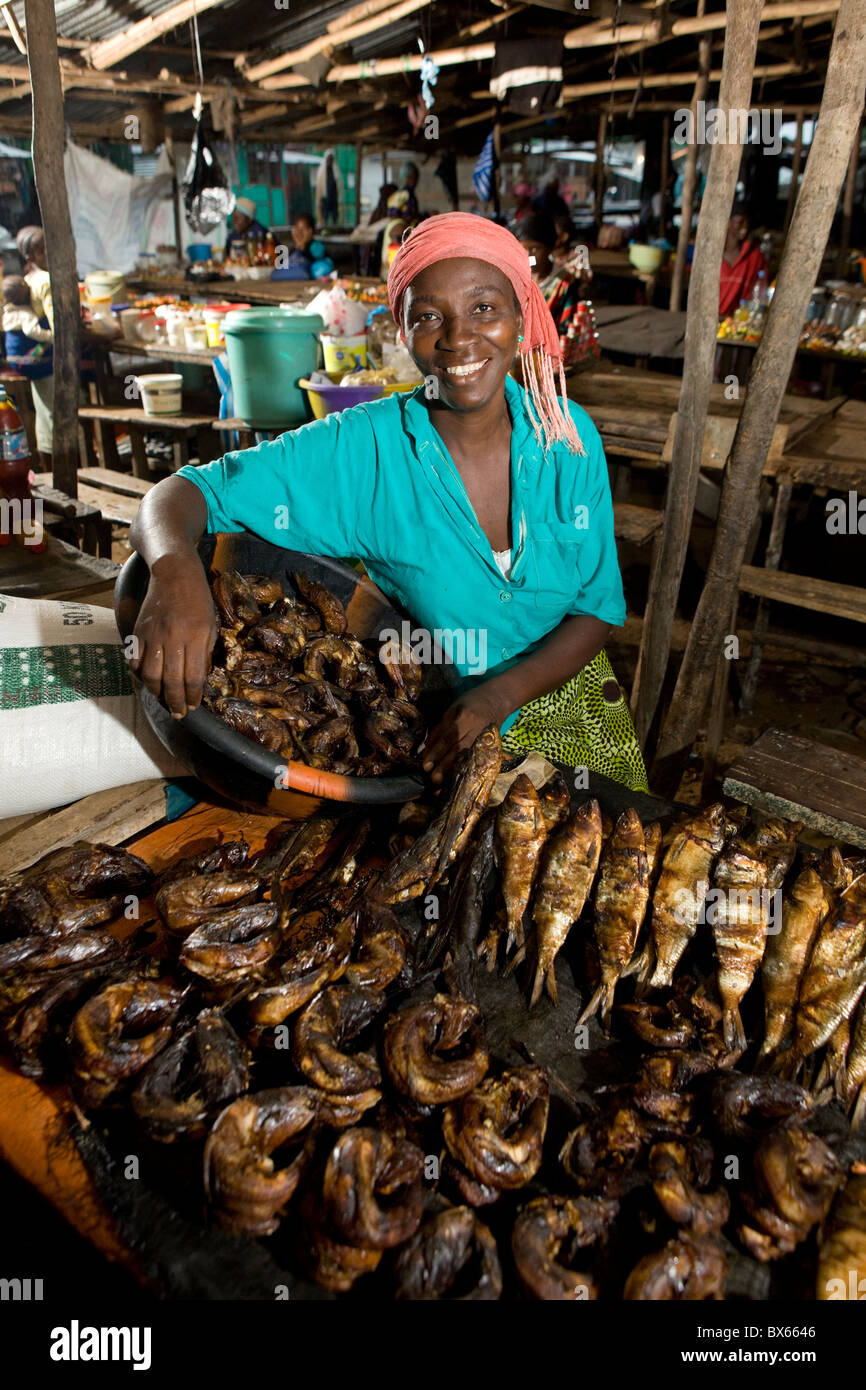 Mrs. Annie Walker sells fish in the market in Monrovia, Liberia after receiving a microfinance loan. - Stock Image