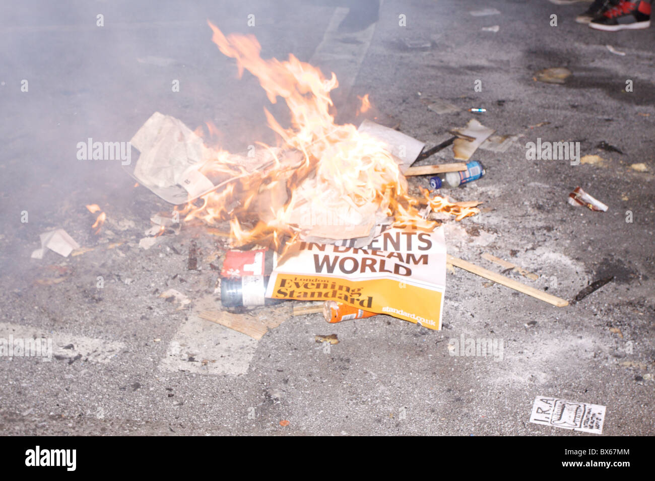 A small fire is made as students protest against rise in tuition fees in Whitehall, central London. - Stock Image