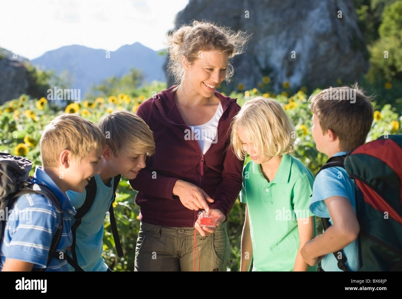 Woman explaining a compass to boys - Stock Image