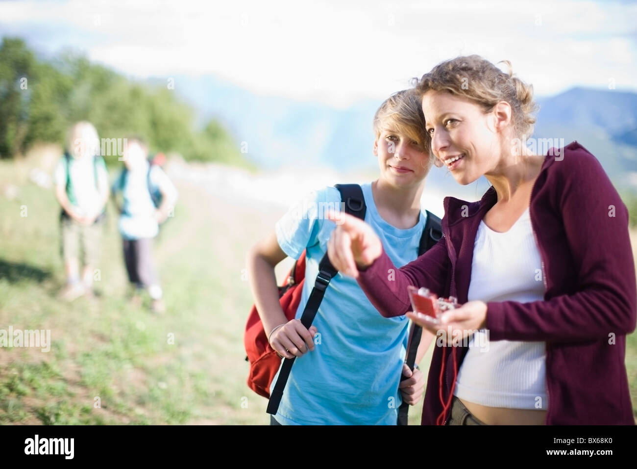 Woman watching a compass with boy - Stock Image