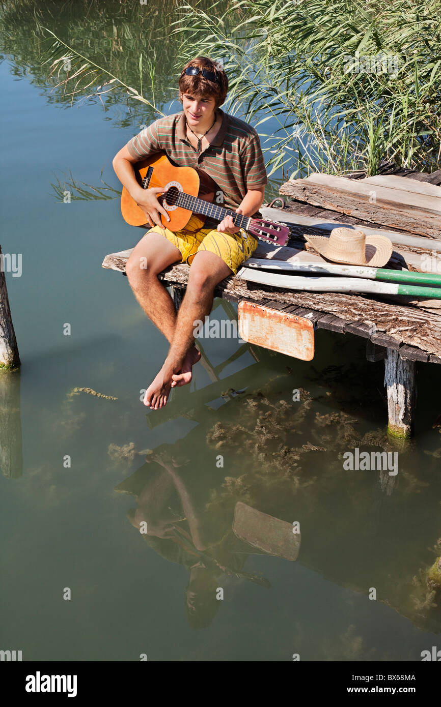 Man sitting on jetty playing a guitar - Stock Image