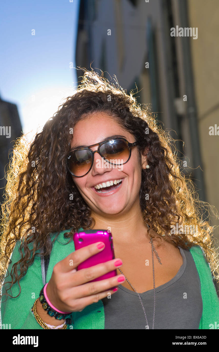 Woman laughs at cell phone in street - Stock Image