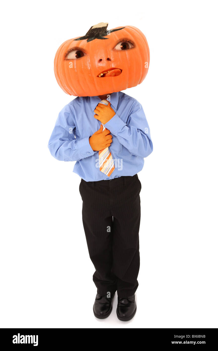 Adorable 7 yaer old pumpkin head boy in suit fixing tie over white background. - Stock Image
