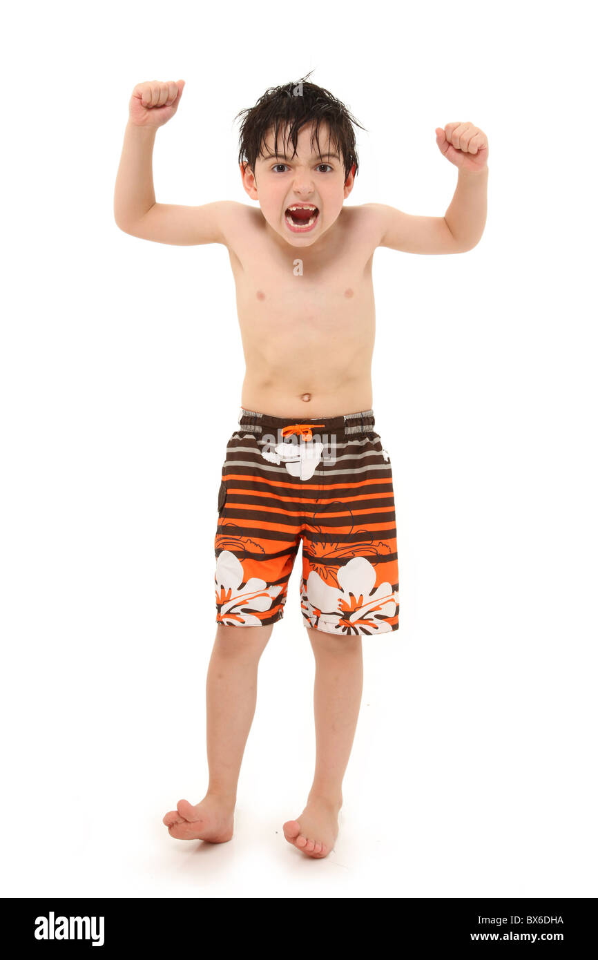 Adorable seven year old french american boy in swim suit and wet hair making silly faces. - Stock Image