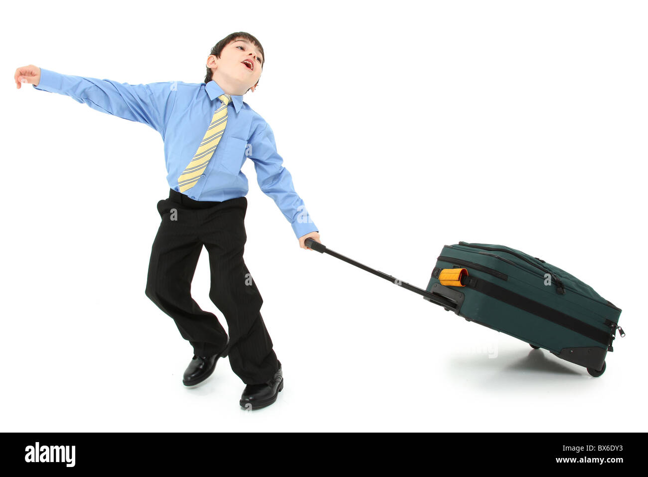 Adorable seven year old french american boy in suit struggling with large suitcase over white background. - Stock Image
