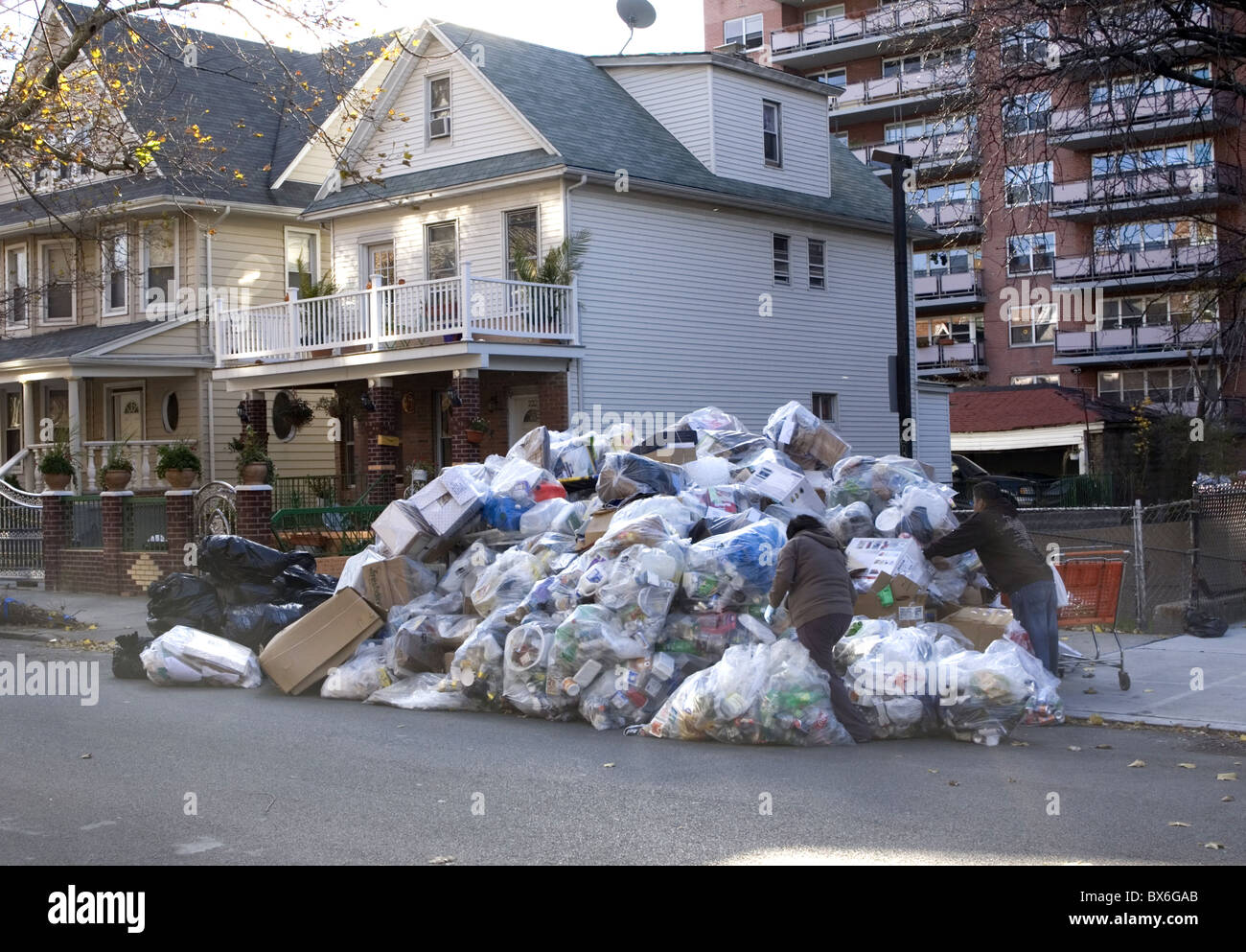 Mountains of recyclable garbage waiting to be picked up from building in background in Brooklyn, New York - Stock Image