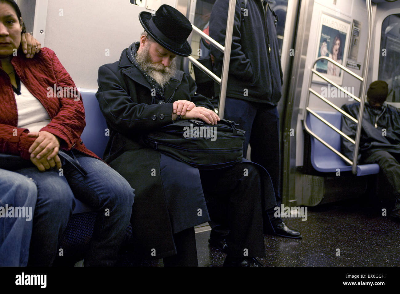 Tired Orthodox Jew rides the subway from Manhattan home to Brooklyn. - Stock Image