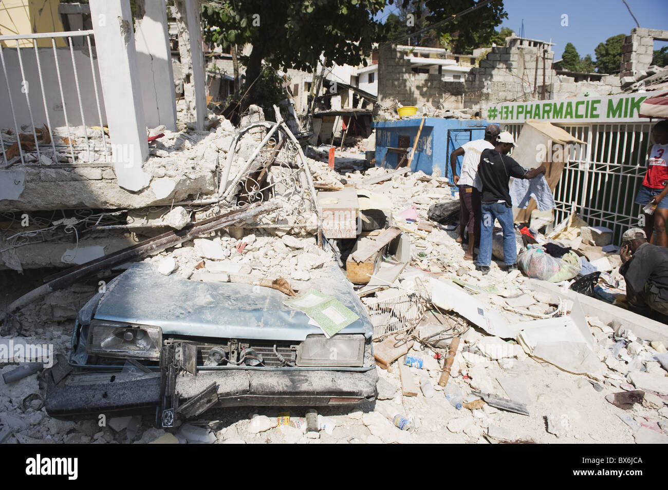 Damaged car and buildings, January 2010 earthquake, Montana Estate, Port au Prince, Haiti, West Indies - Stock Image