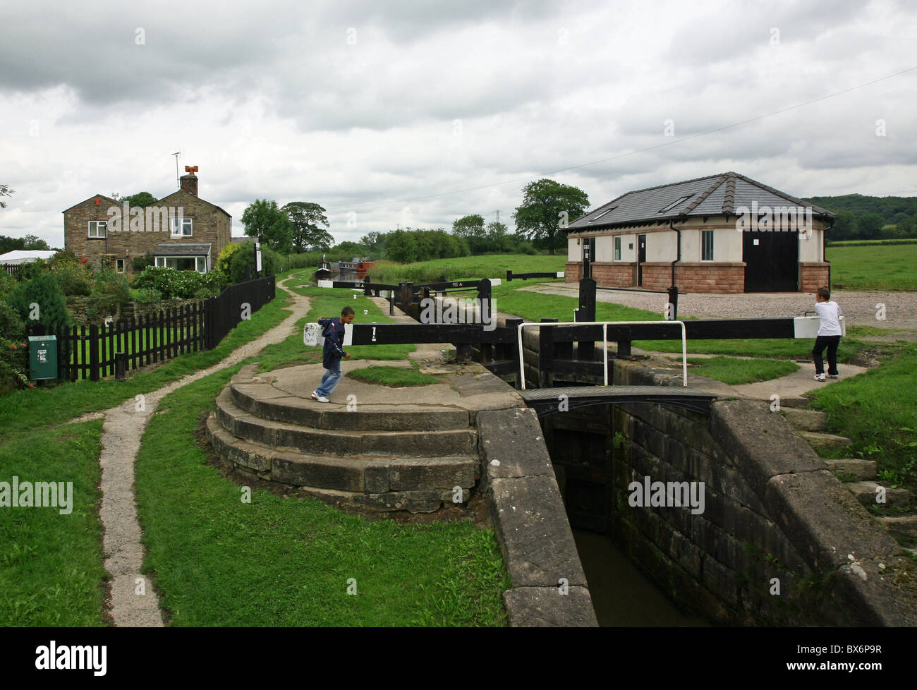 2 young boys opening the lock gates at Bosley Locks on the Macclesfield Canal - Stock Image