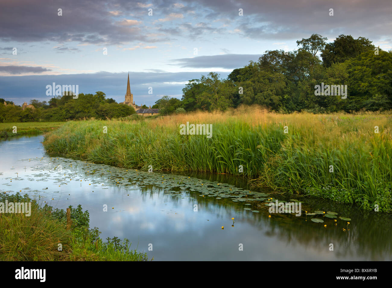 Burford Church spire reflected in the River Windrush watermeadows, Burford, The Cotswolds, Oxfordshire, England. - Stock Image