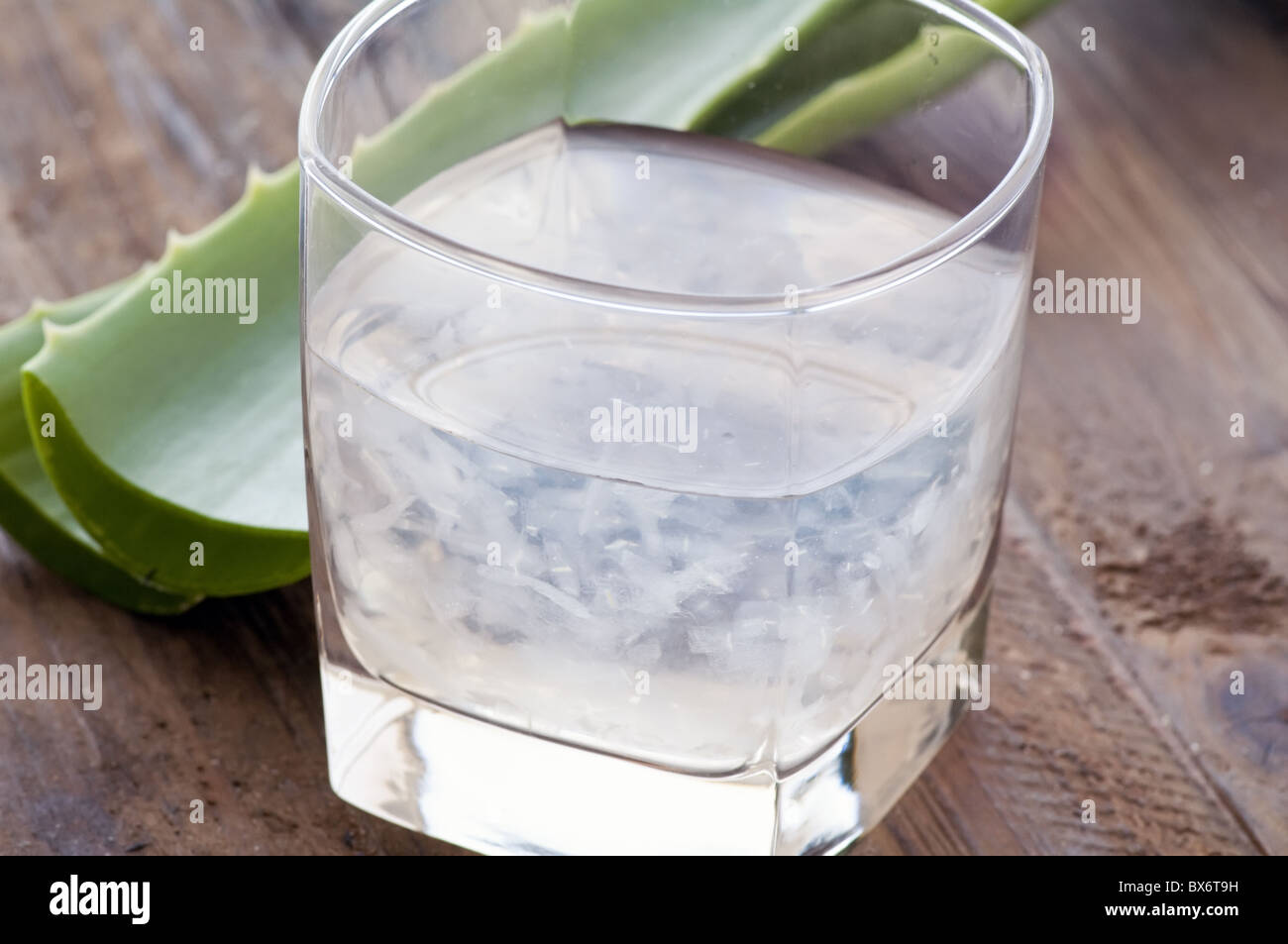 Glass with aloe drink and leaf as closeup on old wood - Stock Image