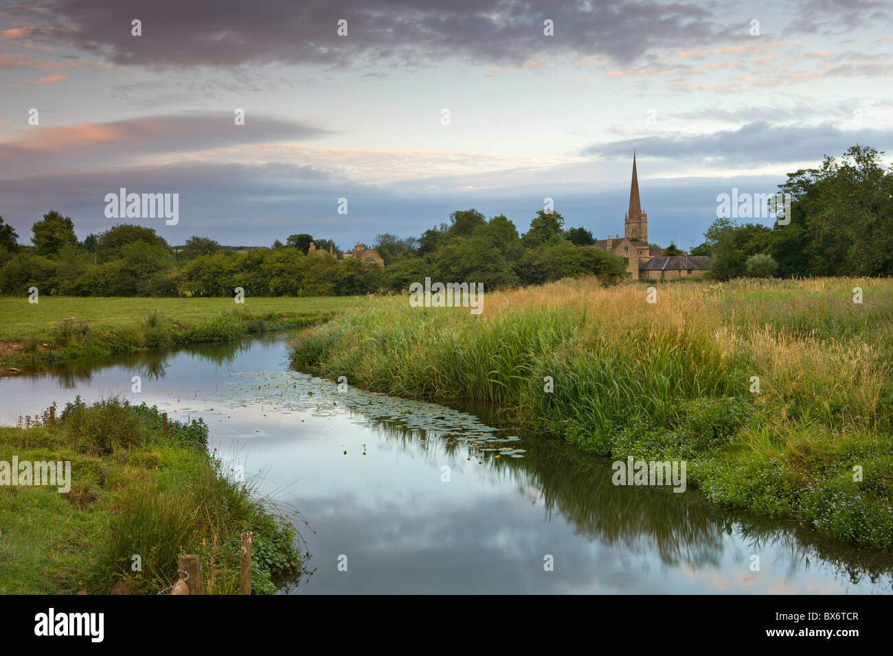 Burford Church and the River Windrush watermeadows at Burford, The Cotswolds, Oxfordshire, England. Summer (July) - Stock Image