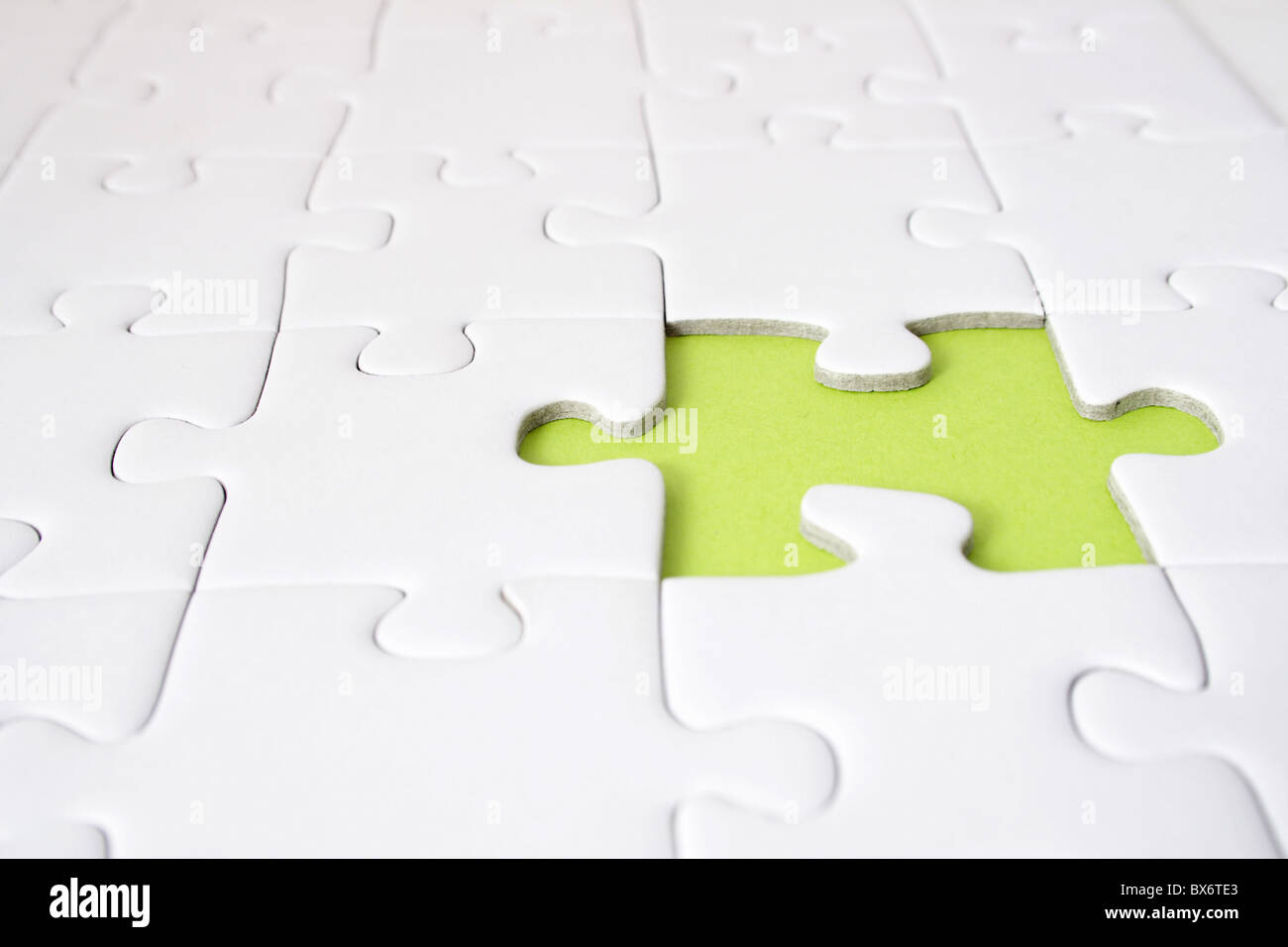 A single green gap in a plain white puzzle game. - Stock Image