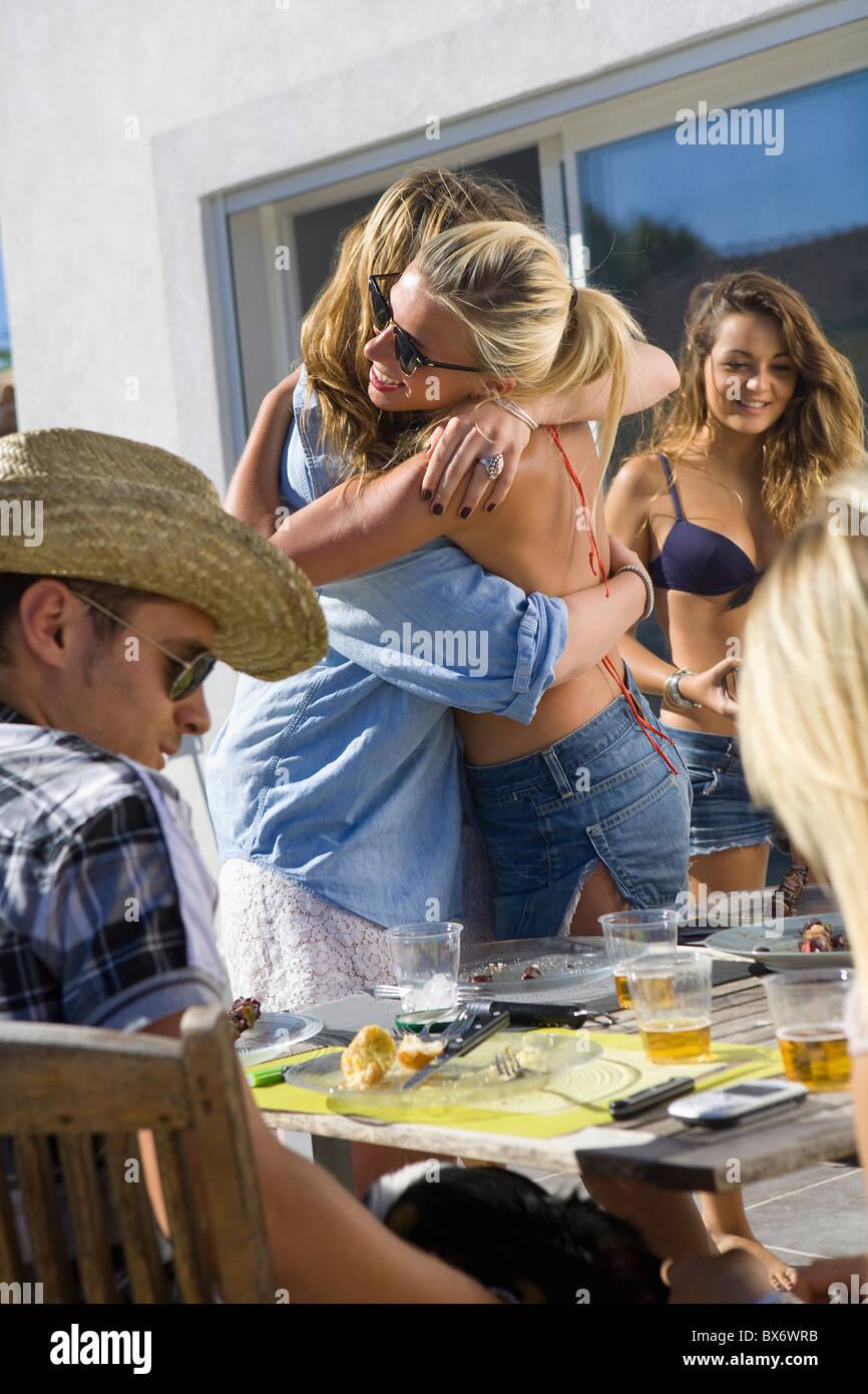 Teen girl hugs teen girl at BBQ table - Stock Image