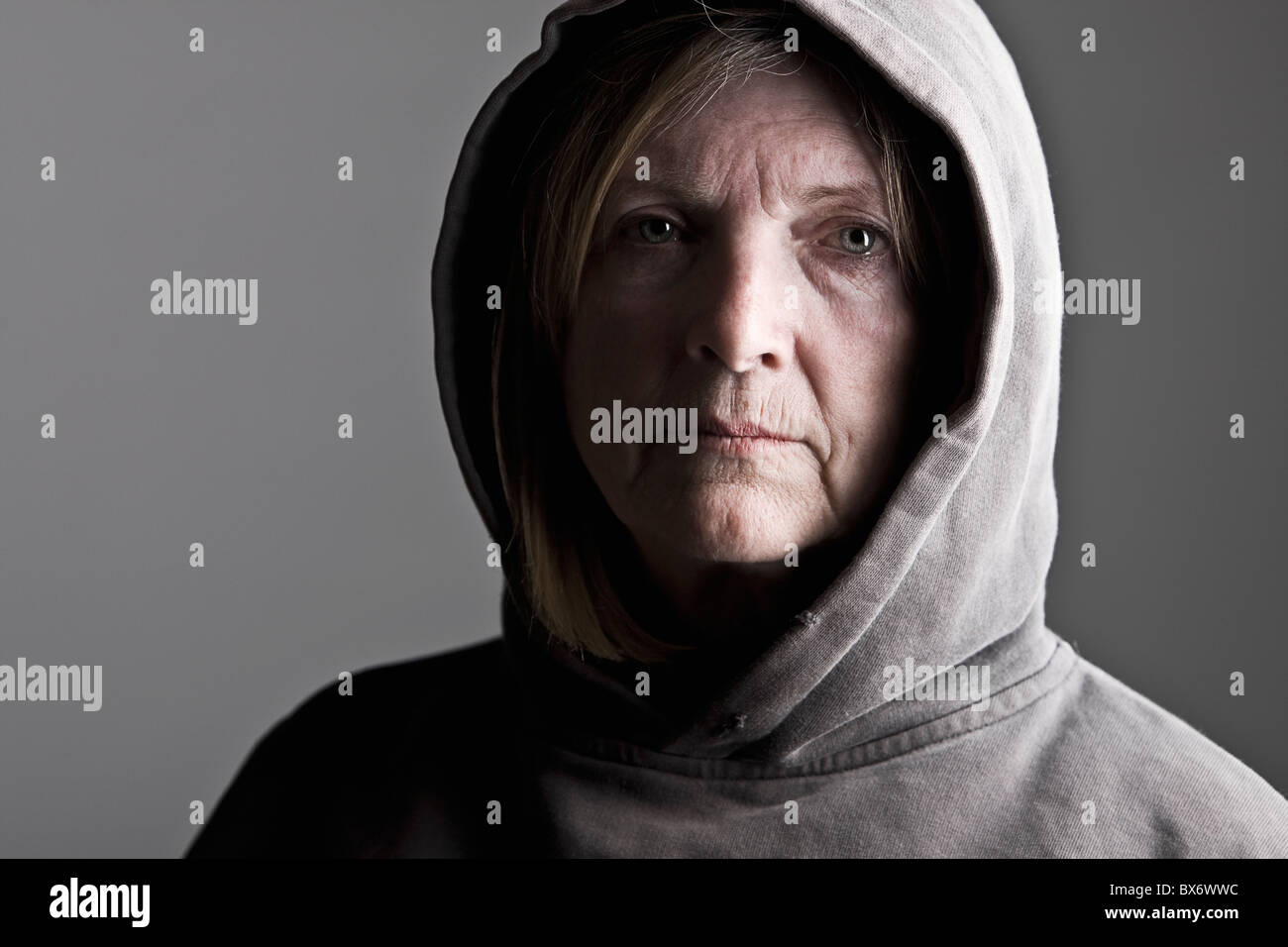 Shot of a Senior Lady in Hooded Top against Grey Background - Stock Image