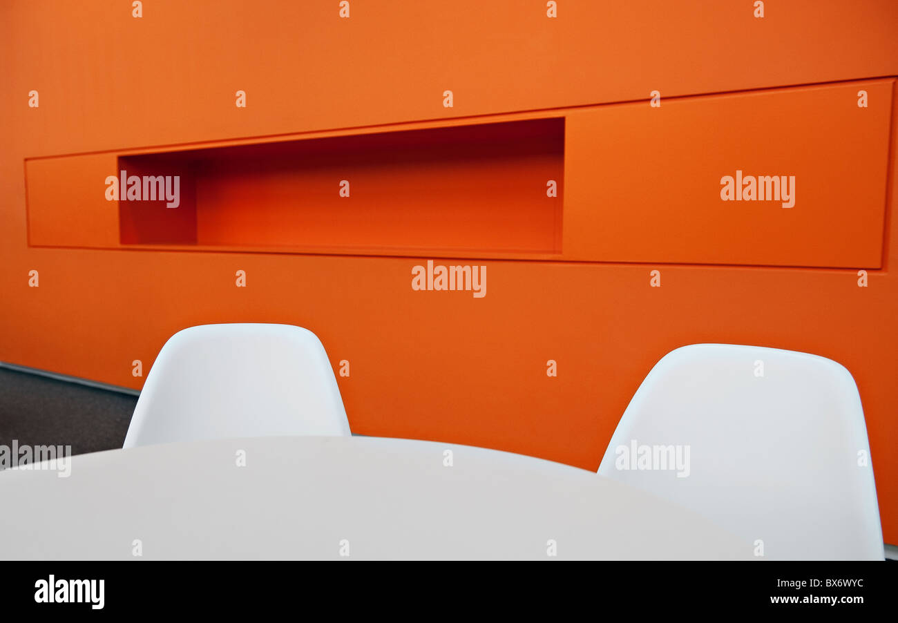 Very colourful ultra modern minimalistic designer office furniture in a modern office block environment - Stock Image