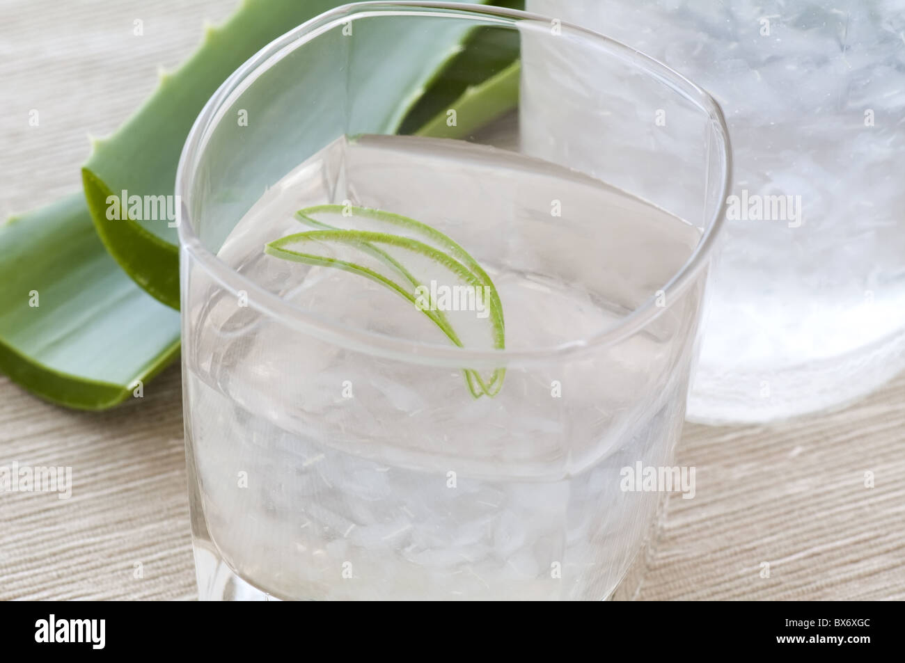 Glass with aloe drink and leaf as closeup - Stock Image