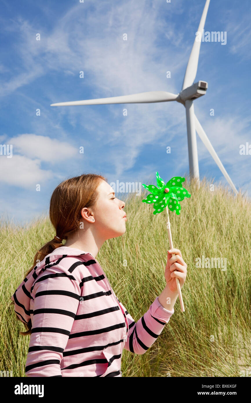 Girl blowing little windmill on beach - Stock Image