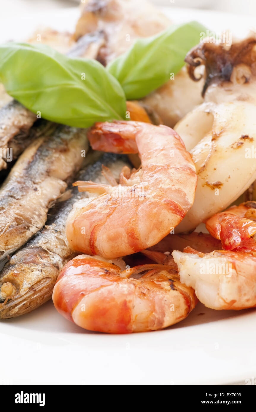 Fried seafood with anchovies and basil as closeup on a white plate - Stock Image