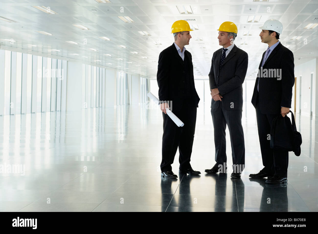 Three executives in hardhats in empty office space - Stock Image