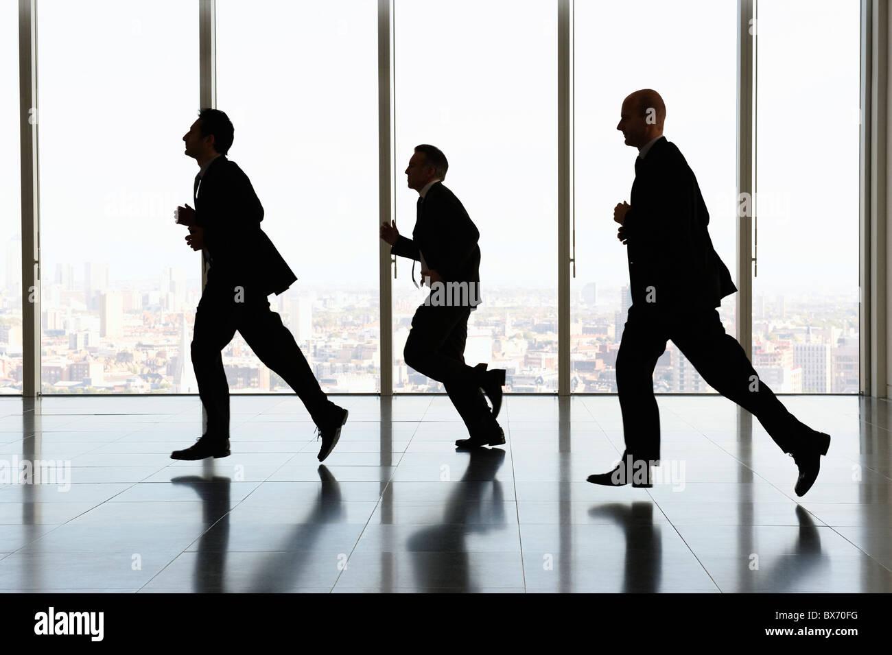 Businessmen running past window, city landscape in background - Stock Image