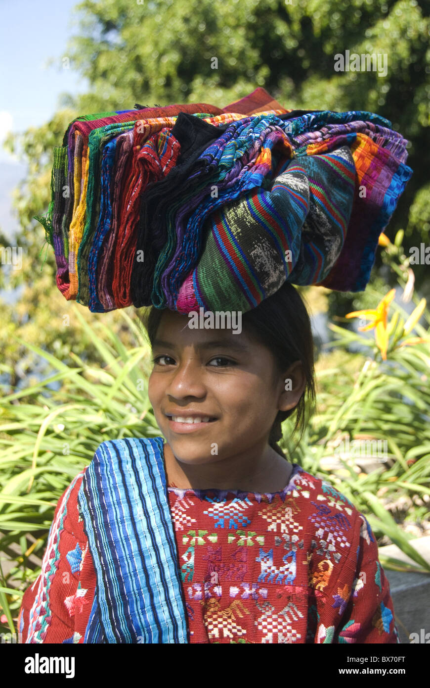 Indigenous girl carrying textiles for sale on her head, Lake Atitlan, Guatemala, Central America - Stock Image