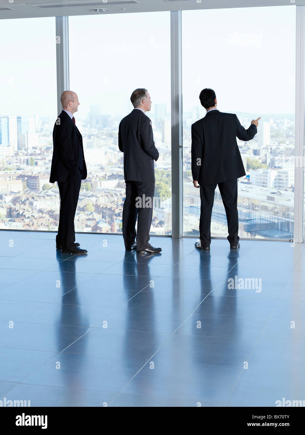Three executives looking at city landscape in empty office space - Stock Image