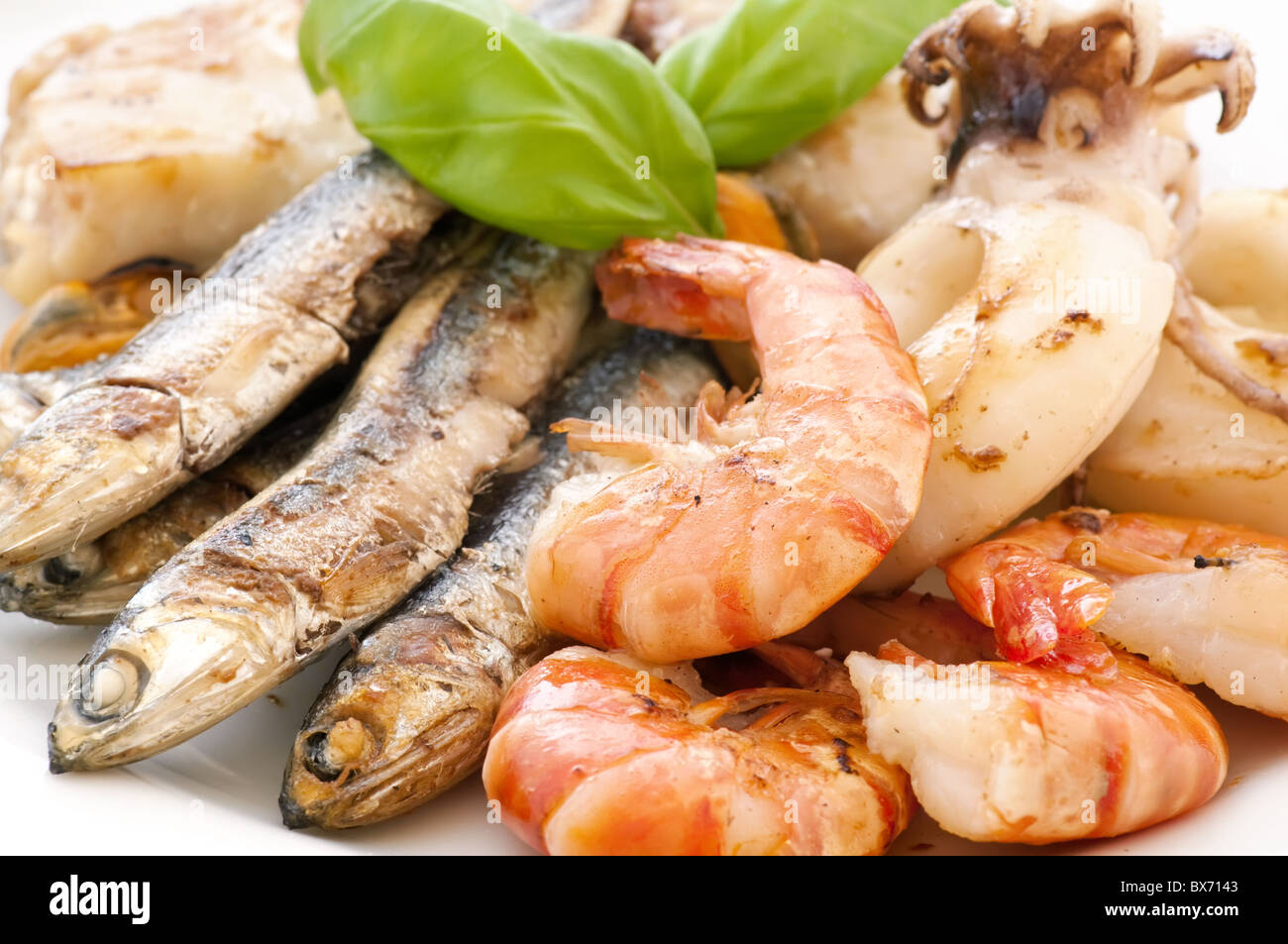 Fried seafood with anchovies and fish as closeup on a white plate - Stock Image