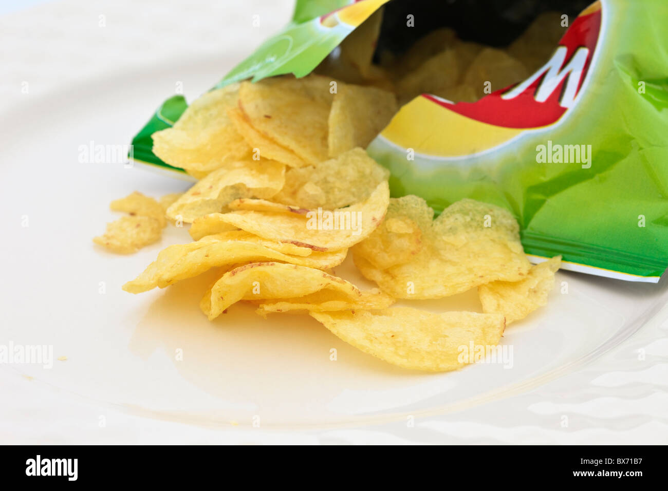 Walkers crisp packet open with crisps spilling out on a plate. - Stock Image