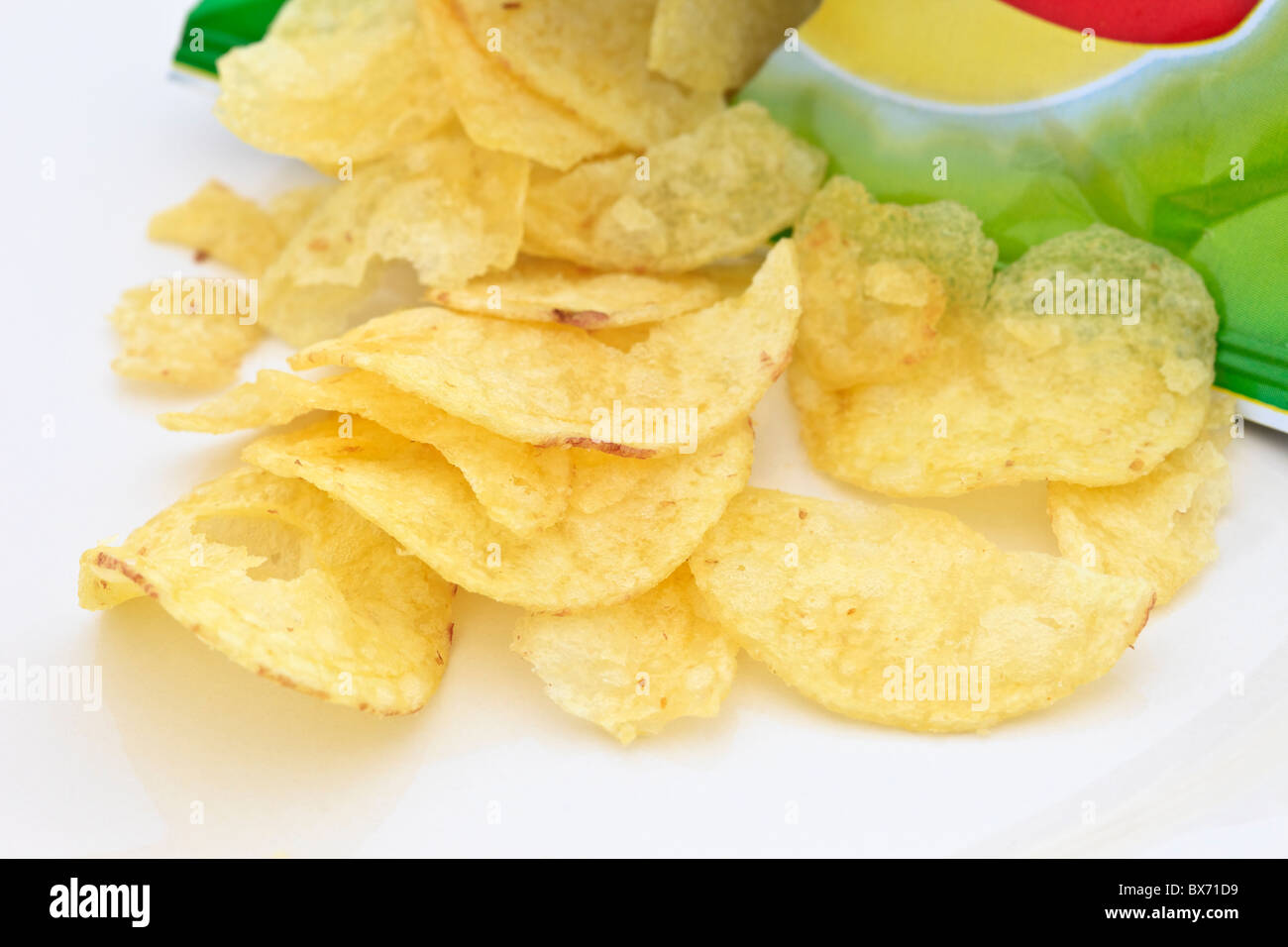 Crisp packet open with crisps spilling out - Stock Image