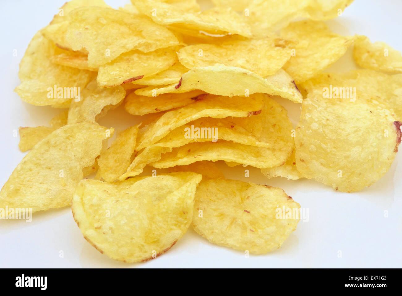 Pile of potato crisps on a plain white background - Stock Image