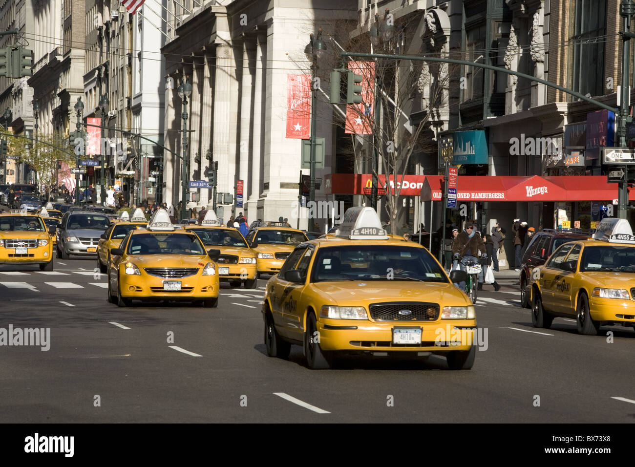 Fleets of yellow cabs dominate 5th Avenue in New York City. - Stock Image