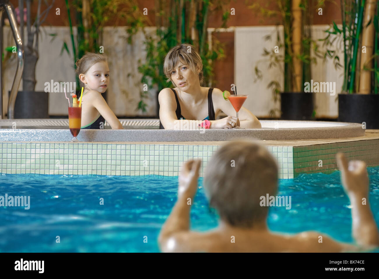 Happy attractive family relaxing by the pool - Stock Image